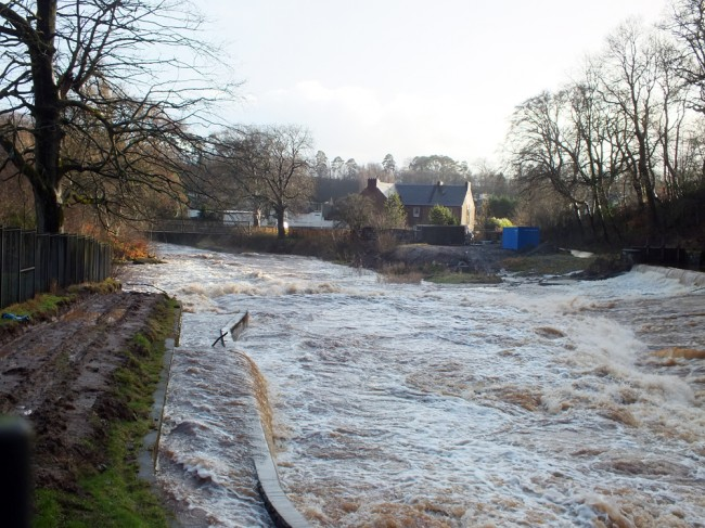 looking down the weir and fish pass. The orifice in the top chamber appears to be blocked causing water to spill over the sides of the pass.