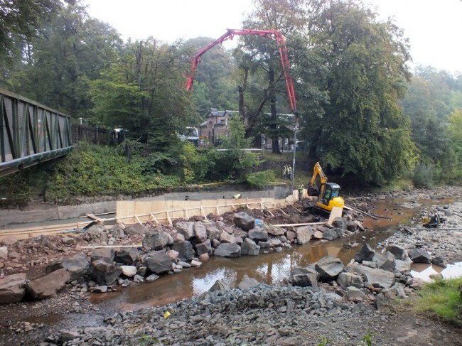 The concrete pumping operation as the last section is completed. The river bed has been scraped and piled behind the shuttering to add strength