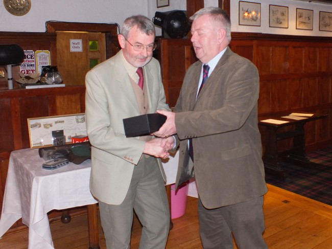 Trust Chairman Bill Stafford presenting Alex Anderson with a pair of whisky glasses at the start of the evening