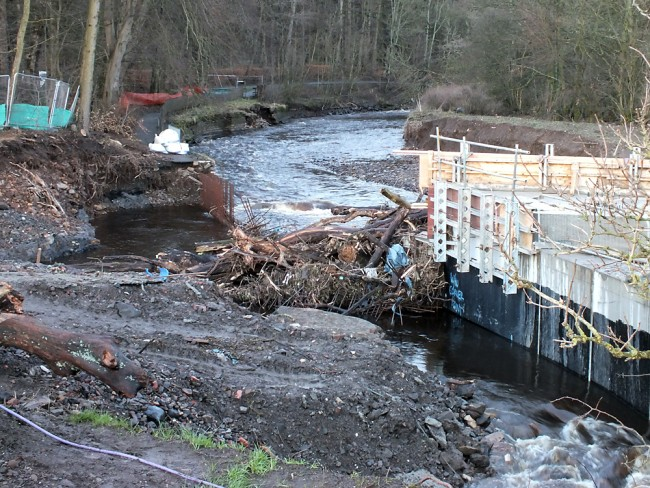 The erosion caused by the blockage can be seen on both banks where the flow diverted around the structure. The steelwork reinforcement can be seen cover with tree trunks and branches and may require some straightening before the work can continue. Upstream, damage to the wall on the Dean Castle bank can be seen in this photo