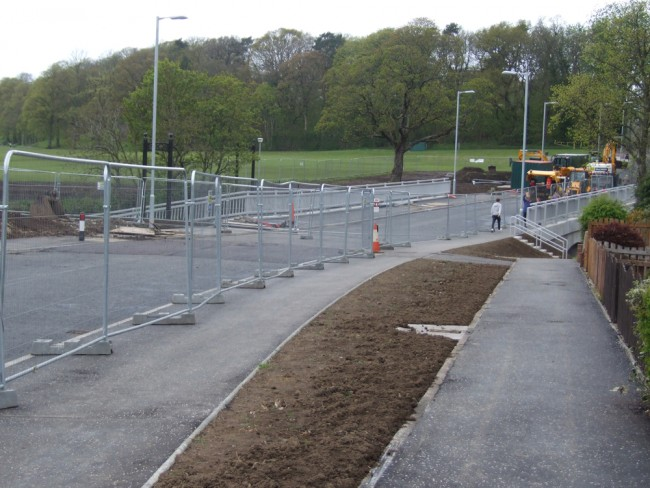 The road has been resurfaced and there can be little left to do but remove the barriers and allow the traffic to flow.