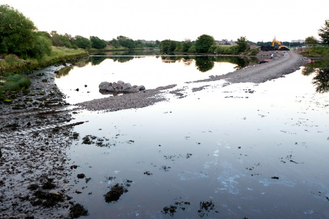 Low tide and the incomplete road is a complete barrier across the river except for 6 small and inadequate pipes near the inside of the bend.